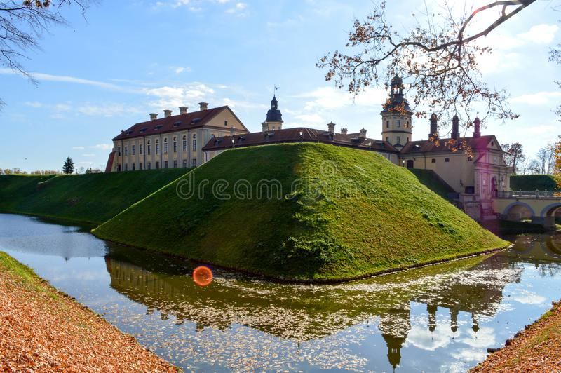 Gammal forntida medeltida slott med spiers och torn, väggar av stenen och tegelsten som omges av en skyddande vallgrav med vatten royaltyfria foton