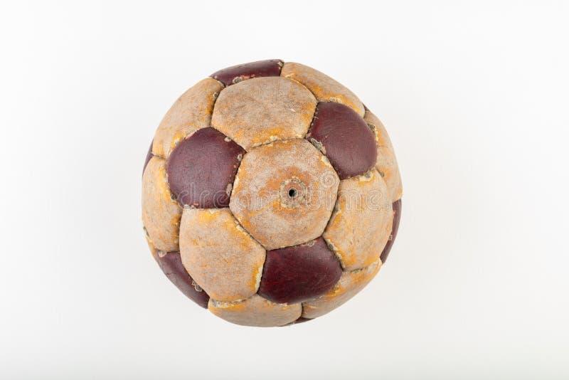 Gammal fotbollboll som spelar på benet på en vit tabell Läder och förstörd boll utan luft arkivbild