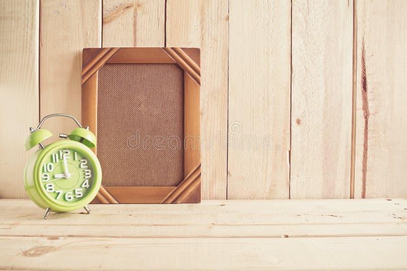 Gammal fotoram och klocka på trätabellen över wood bakgrund arkivfoton