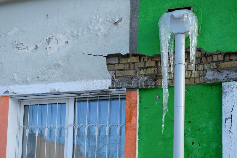 Gammal fundament och murbrukvägg med sprickor Byggande kräva reparationscloseupen Djupfryst stupränna med istappar arkivfoton