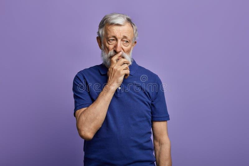 Gammal fundersam man med en hand på hans mun royaltyfri fotografi