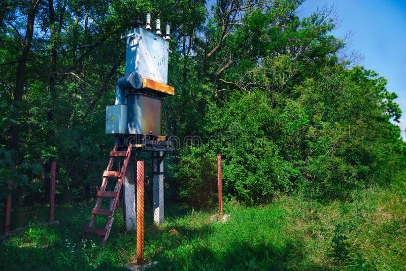 Gammal funktionsduglig lantlig transformator för elektrisk fördelning i den soliga dagen för skog, begreppet av industriellt royaltyfri foto