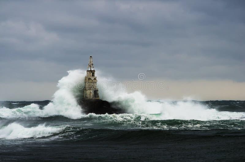 Gammal fyr i havet i stormig dag royaltyfri bild