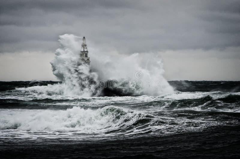 Gammal fyr i havet i stormig dag royaltyfria bilder