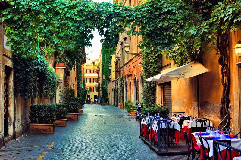 Gammal gata i Rome med lövrika vinrankor och kafétabeller, Italien arkivbild