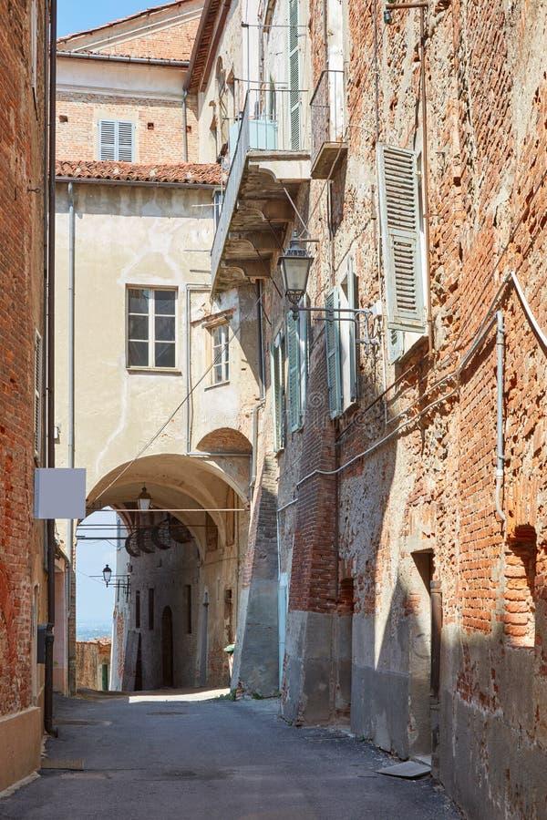 Gammal gata med byggnader för röda tegelstenar och bågen i en sommardag, ingen i Mondovi, Italien arkivbilder