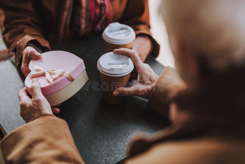 Gammal gentleman som ger gåva till hans fru, medan rymma koppen kaffe arkivfoto