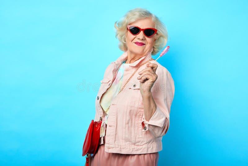Gammal gladlynt lycklig dam med solglasögon som rymmer klubban arkivfoto