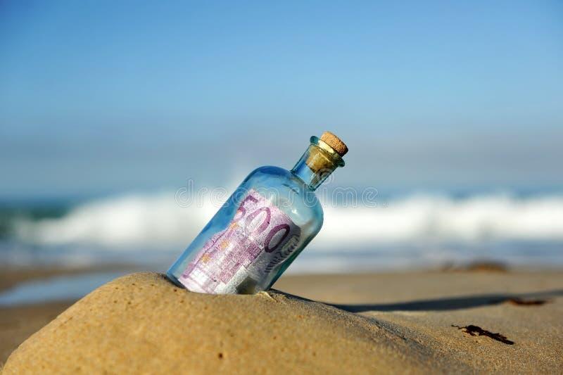 Gammal glasflaska med sedeln för euro 500 inom, sand av stranden royaltyfria foton