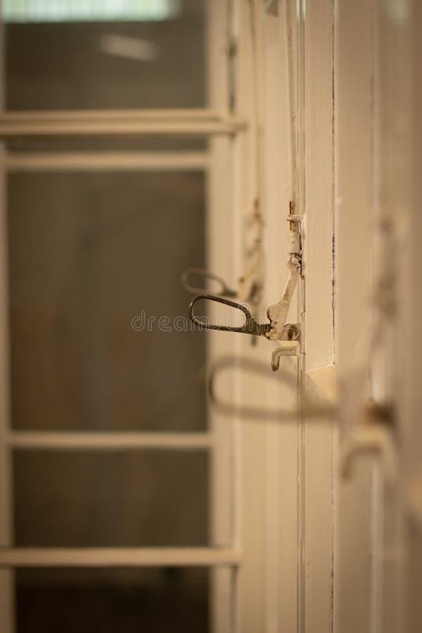 Gammal glasvägg med dörrar, fokus på fönsterhandtaget arkivbilder