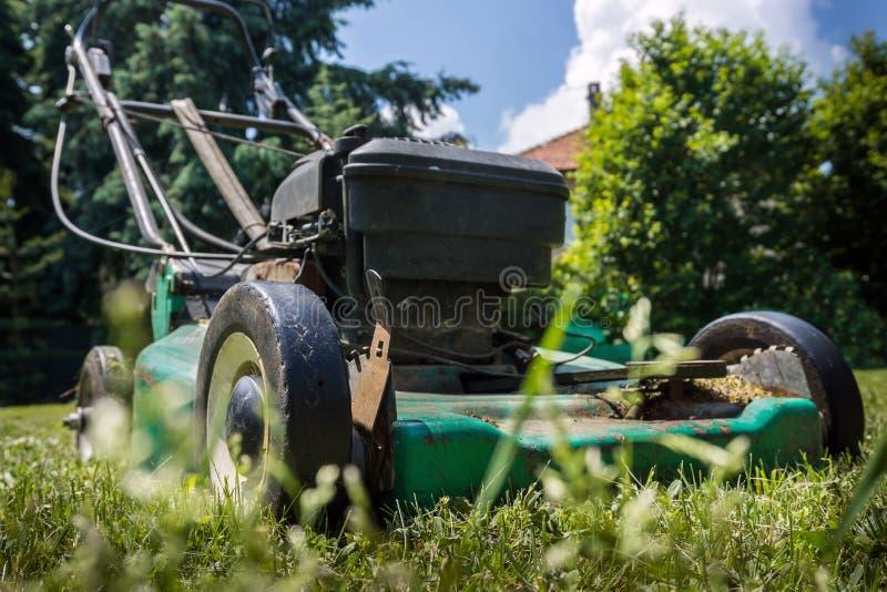 Gammal gräsklippningsmaskin i gård royaltyfri bild