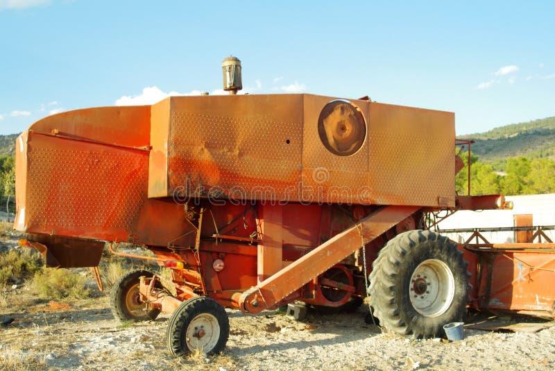 Gammal gräsklippningsmaskin i orange tonaliteter royaltyfri bild