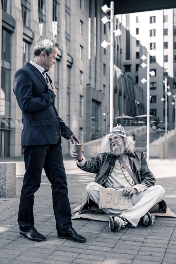Gammal grå färg-haired man som är arbetslös och bor på gatan arkivbilder