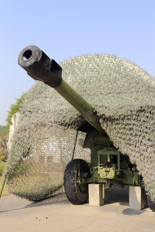 Gammal grön kanon med kamouflage royaltyfri foto