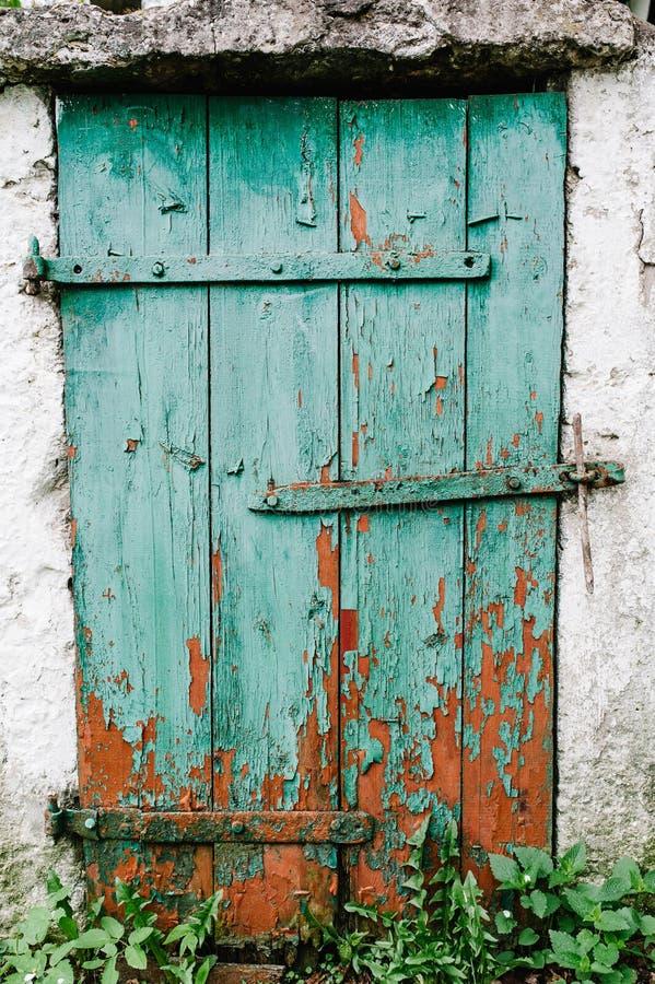 Gammal grön trädörr i en vit vägg _ sprucket Dörren t arkivbilder