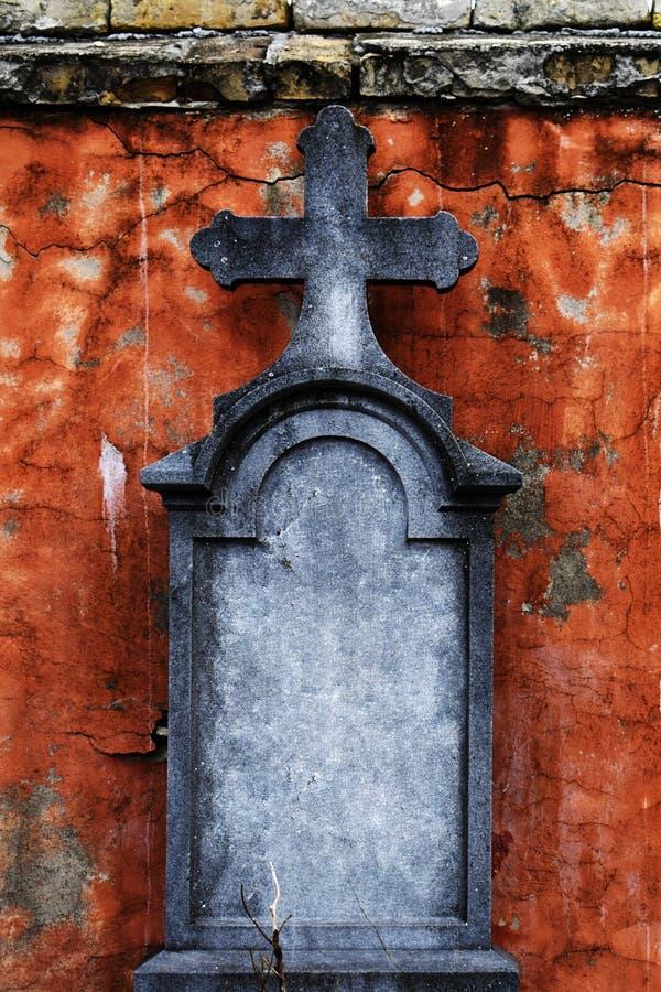 Gammal gravsten med korset framme av att smula fasaden fotografering för bildbyråer