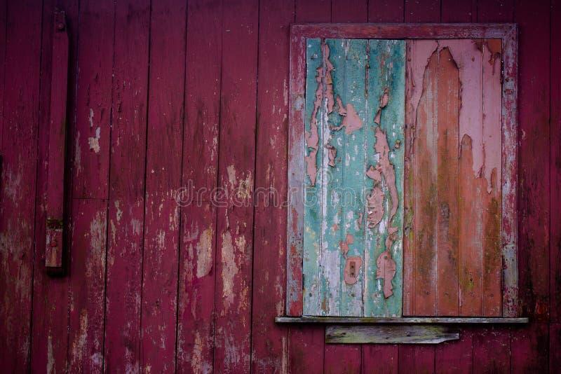 Gammal grunge och den red ut hem- fasaden med det gröna fönstret och röda väggplankor texturerar bakgrund royaltyfria foton