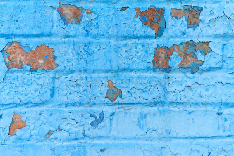 Gammal grungetegelstenvägg av en bakgrund eller en textur som målas i blå målarfärg som knäckte under påverkan av tid och väder royaltyfri fotografi