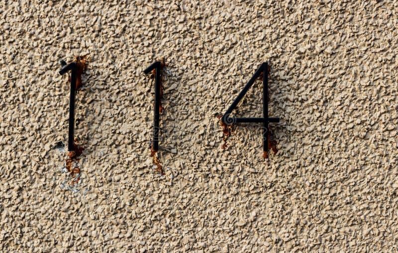 Gammal grungy vit vaggar väggen med numren 114 som limmas i all hast royaltyfri bild
