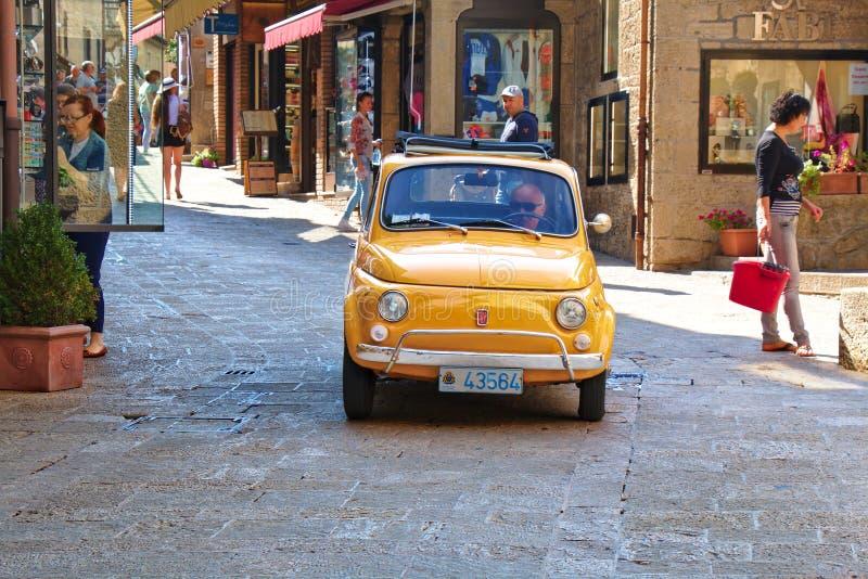 Gammal gul bil Fiat 500 i San Marino, Italien fotografering för bildbyråer