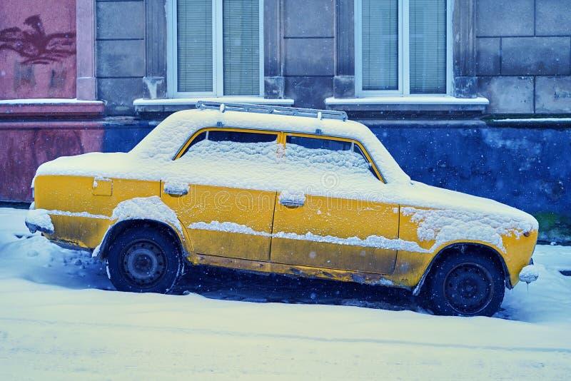 Gammal gul bil som täckas med snö som parkeras på en snöig slutta gata i vinterstad royaltyfri fotografi