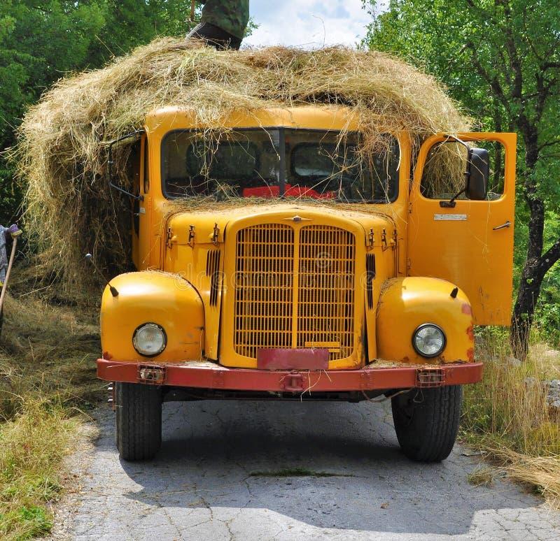 Gammal gul lastbil som laddas med sugrör royaltyfri fotografi