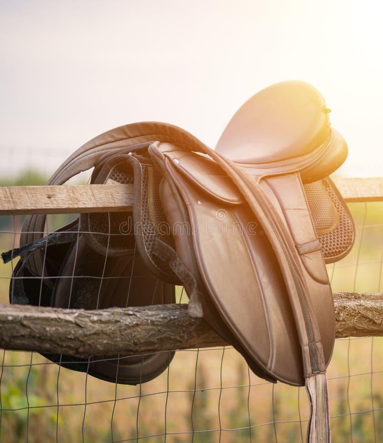 Gammal hästsadel på ett staket fotografering för bildbyråer