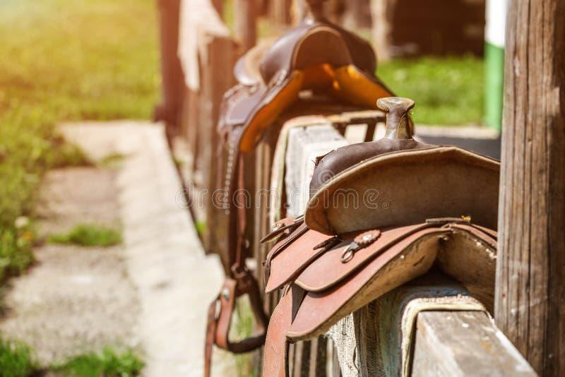 Gammal hästsadel som förläggas på trästaketet bredvid huset som tänds av su fotografering för bildbyråer
