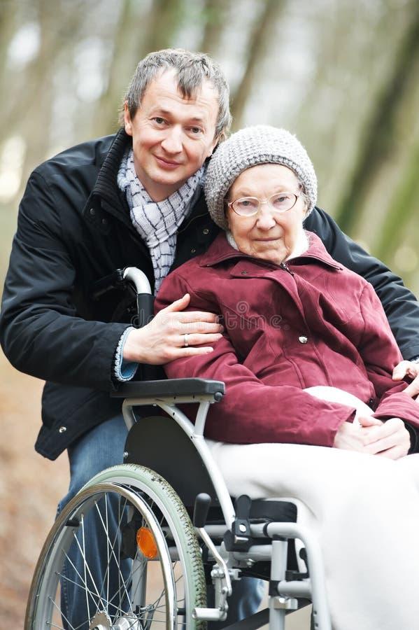 Gammal hög kvinna i rullstol med den försiktiga sonen royaltyfri bild