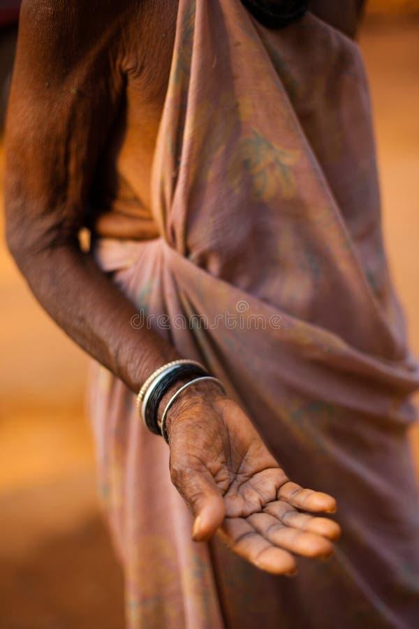 Gammal hög kvinnahand som tigger ut pengar Indien arkivfoton
