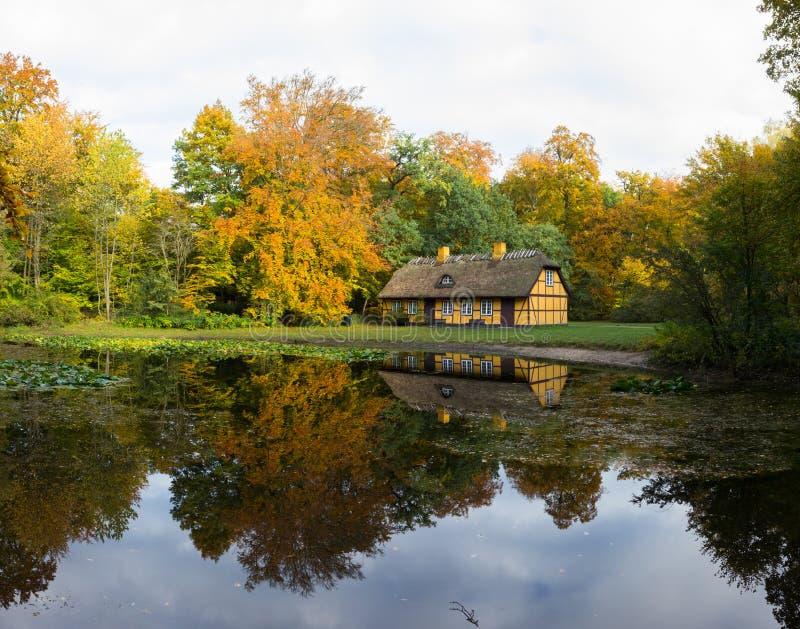 Gammal halva timrat hus med det halmt?ckte taket i Charlottenlund, Danmark arkivfoton