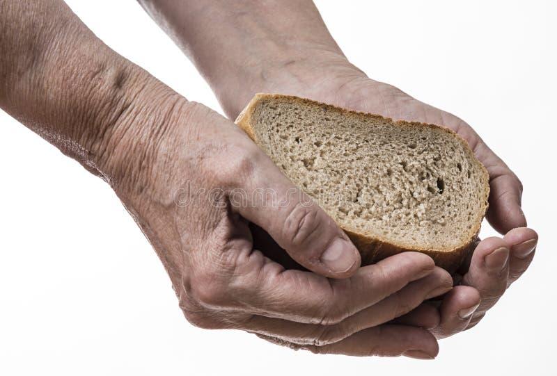 Gammal hand med bröd royaltyfri foto