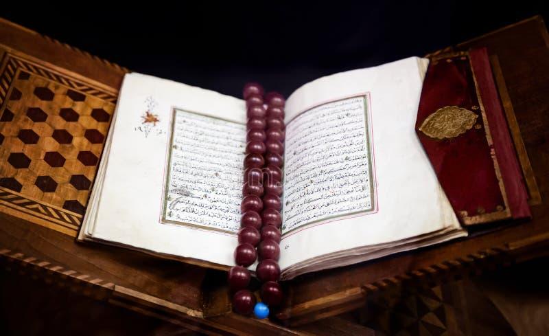 Gammal helig islamisk bokKoranen öppnade i läderband med brunt arkivbilder
