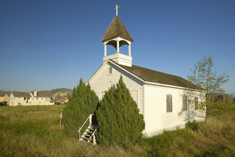 Gammal historisk kyrka nära Somis, Ventura County, CA med sikt av ny hem- konstruktion för encroaching royaltyfria bilder