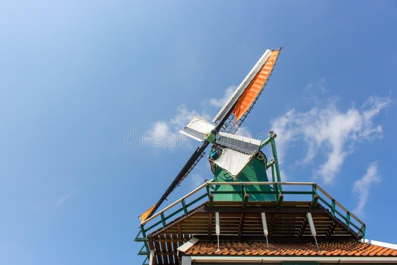 Gammal holländsk väderkvarn i Nederländerna Väderkvarn mot blå himmel med moln Historisk arkitektur i Europa Lantlig holland grän royaltyfri foto