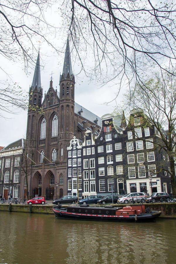 Gammal hus och kyrka på den Amsterdam kanalen fotografering för bildbyråer