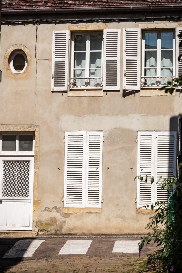 Gammal husfasad med slutaren och den vita dörren arkivbild