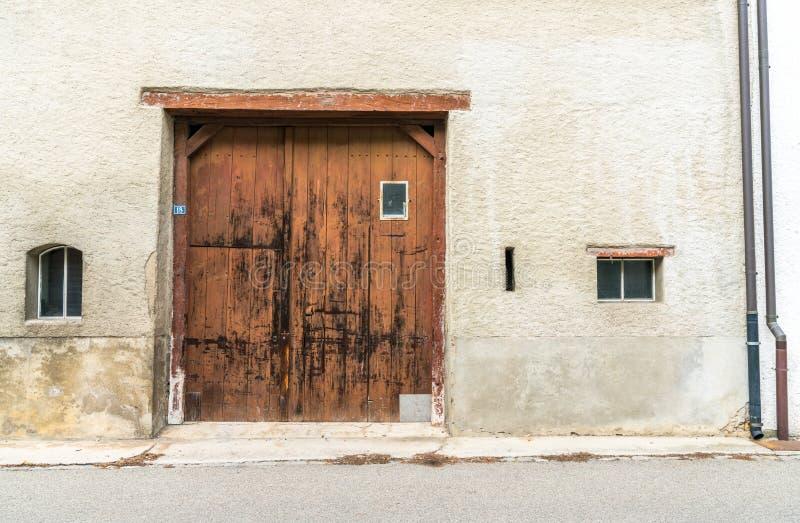 Gammal husfasad med urblekt och kanstött målarfärg och murbruk och den stora träporten i de mellersta och lilla fönstren på sidan royaltyfri fotografi