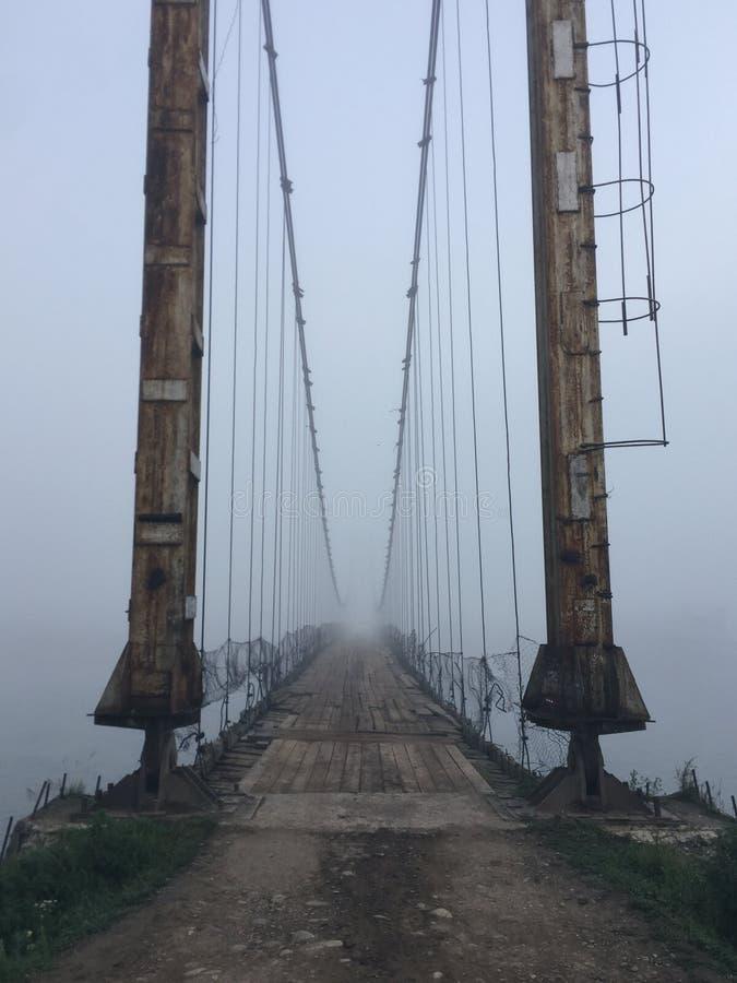 Gammal ing?ng f?r upph?ngningbro i dimma Altai bybro Tidig dimmig morgon royaltyfri bild