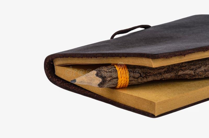 Gammal isoalated bok och blyertspenna arkivbilder