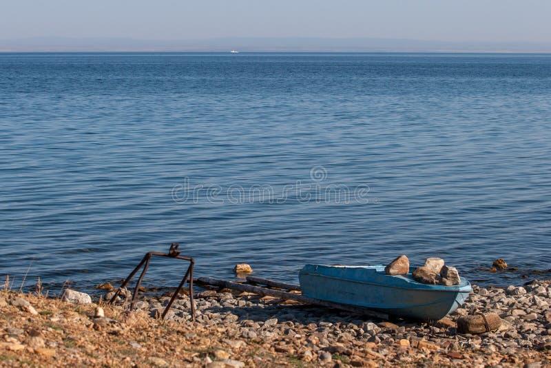 Gammal järnfiskebåt på kusten av det blåa Laket Baikal Pressande ner av stora stenar arkivbild