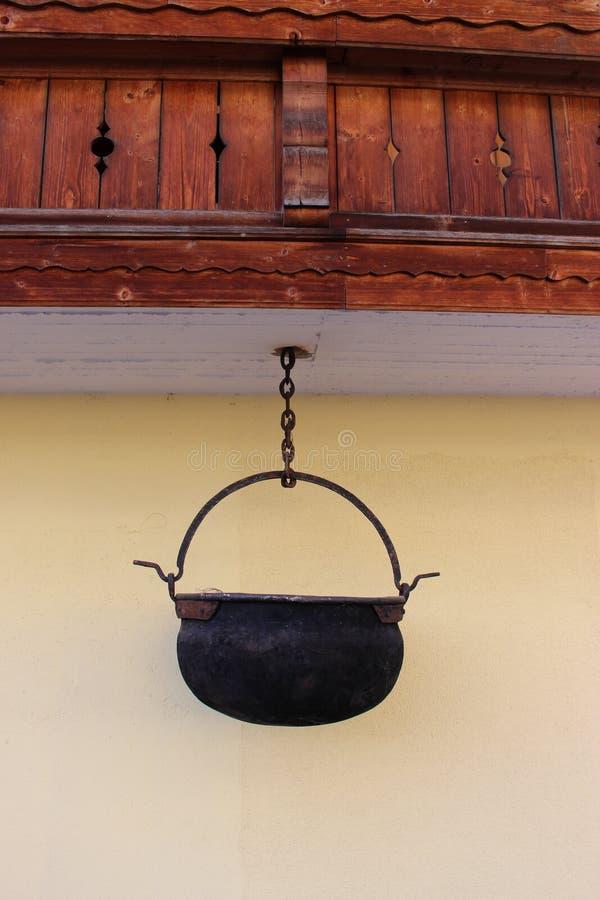 Gammal järnkittel som hänger under en balkong royaltyfria bilder