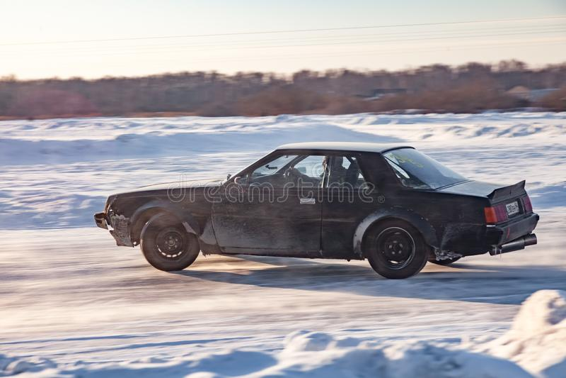 Gammal japansk bil Nissan som förbereds för att springa drev på isen på en djupfryst sjö, att driva och inflyttning en skidder i  royaltyfri foto