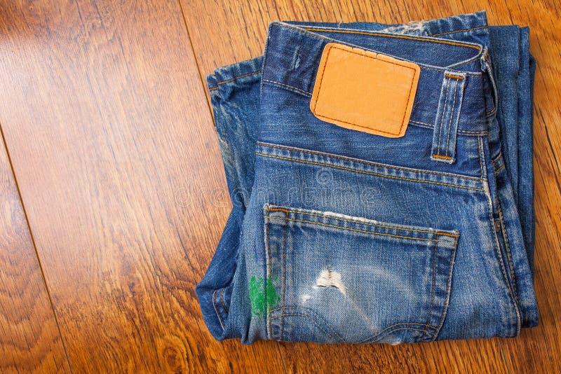 Gammal jeans med den bruna etiketten på bältet suddigt med gräsplan p arkivbilder