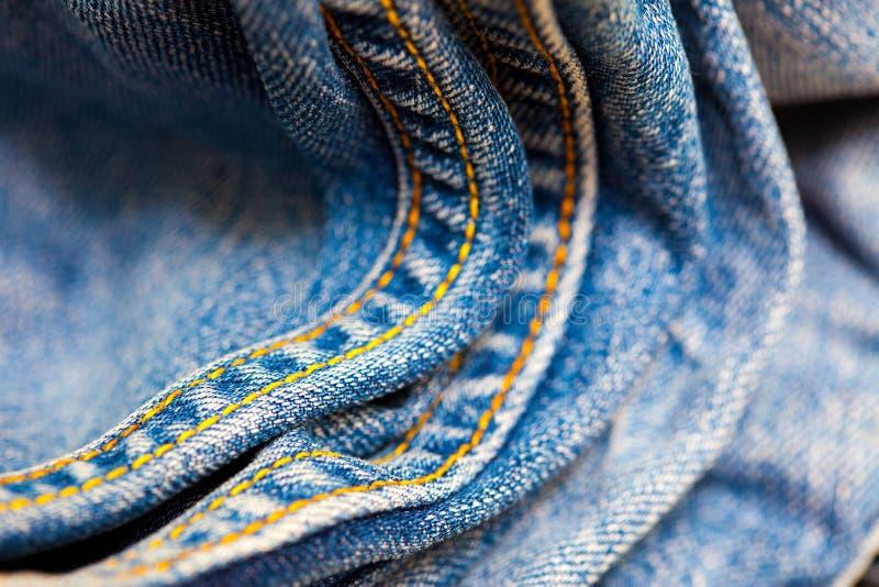 Gammal jeans med den gula sy tråden arkivbild