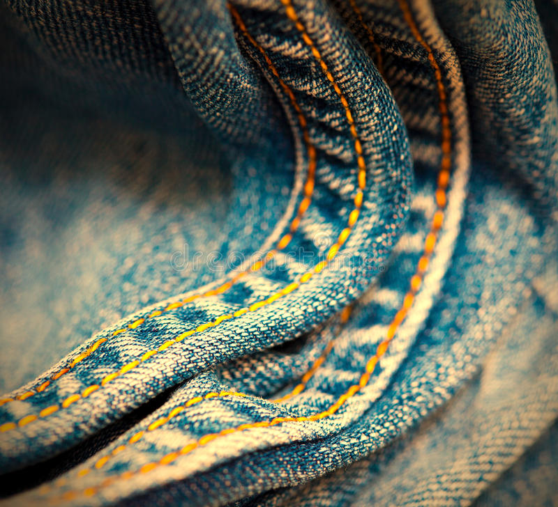 Gammal jeans med den gula sy tråden royaltyfria bilder