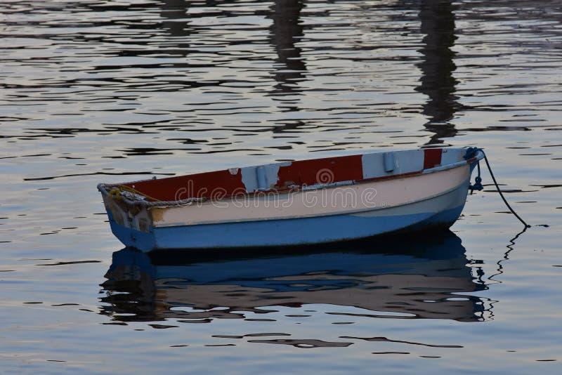 Gammal jolle på lugna vatten fotografering för bildbyråer