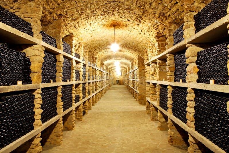 Gammal källare av vinodlingflaskorna av vin i de framtida enorma warena royaltyfria foton