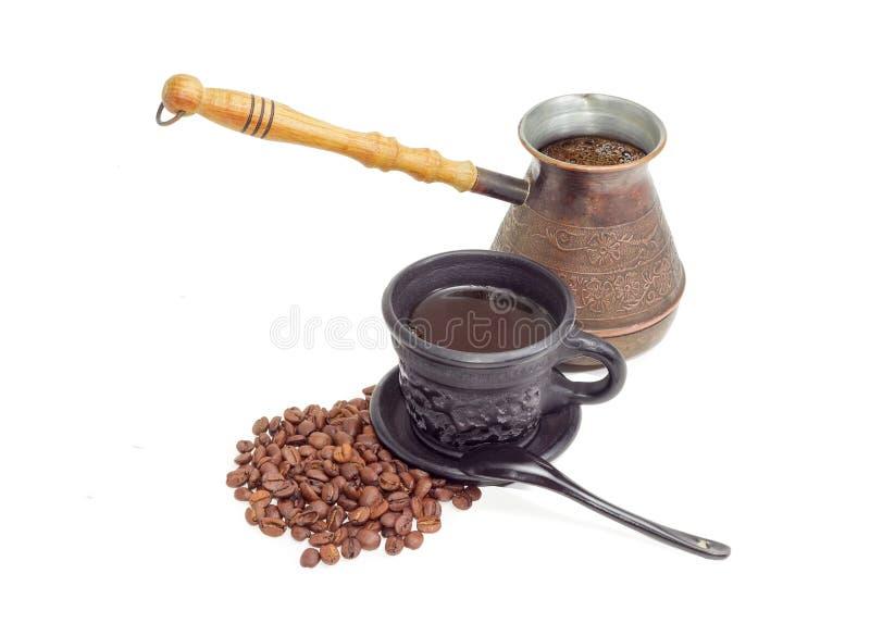 Gammal kaffekruka, svart keramisk kopp med kaffe, kaffebönor arkivfoto