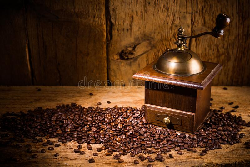 Gammal kaffekvarn med nya grillade bönor på lantlig gammal tappningekbakgrund royaltyfri bild